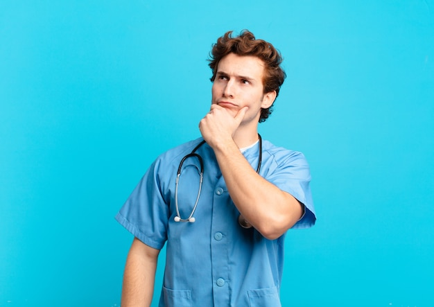 Jonge verpleegster die denkt, zich twijfelachtig en verward voelt, met verschillende opties, zich afvragend welke beslissing hij moet nemen