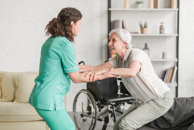 Jonge verpleegster die gehandicapte hogere vrouw bijstaan