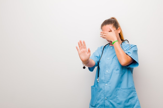 Jonge verpleegster die gezicht behandelt met hand en andere hand vooraan zet om camera tegen te houden, weigert foto's of beelden over witte muur