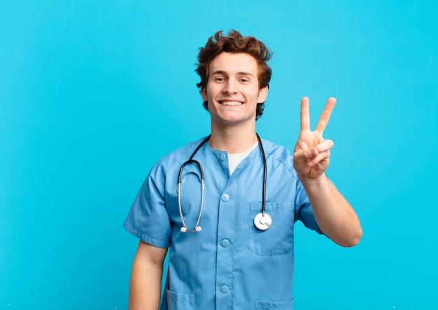 Jonge verpleegster die lacht en er gelukkig, zorgeloos en positief uitziet, gebarend overwinning of vrede met één hand