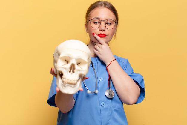 Jonge verpleegster die menselijke schedel vasthoudt