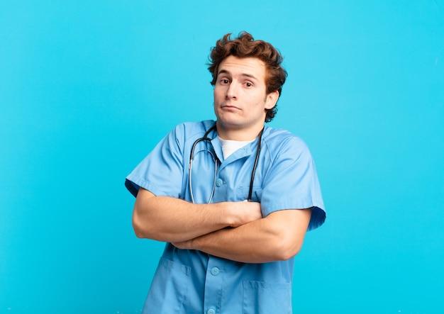 Jonge verpleegster die zijn schouders ophaalt, zich verward en onzeker voelt, twijfelt met gekruiste armen en een verbaasde blik
