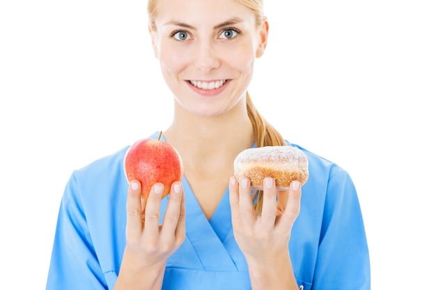 Jonge verpleegster die zoet voedsel en appel houdt die over witte achtergrond wordt geïsoleerd