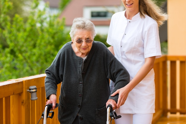 Jonge verpleegster en vrouwelijke oudste met wandelend kader