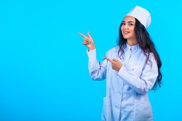 Jonge verpleegster in geïsoleerd uniform kijkt opgewekt en wijst naar iets.