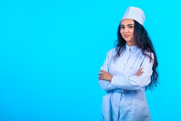 Jonge verpleegster in geïsoleerde uniform sluit armen en glimlacht