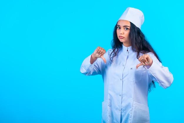 Jonge verpleegster in geïsoleerde uniform ziet er depressief uit en maakt een negatief teken.