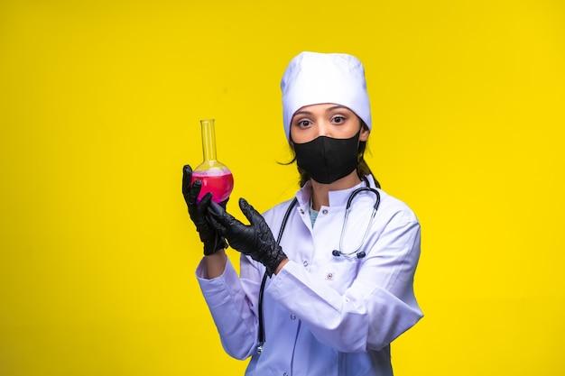 Jonge verpleegster in gezicht en handmasker houdt een testfles met roze vloeistof.