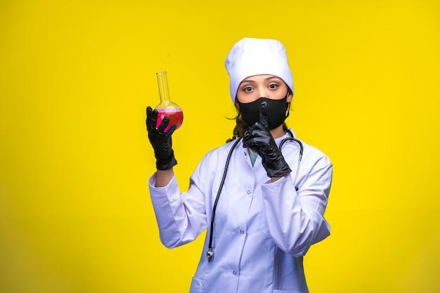 Jonge verpleegster in gezicht en handmasker houdt een testfles op geel.