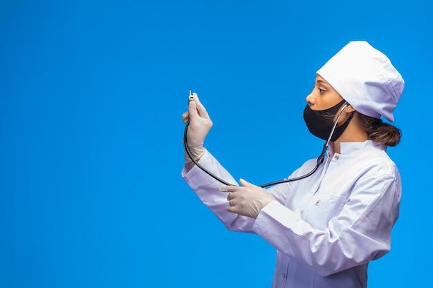 Jonge verpleegster in gezichtsmasker en handhandschoenen controleert de patiënt met een stethoscoop.