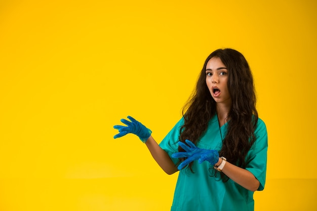 Jonge verpleegster in groene uniforme en plastic handschoenen die verbaasd gezicht maken