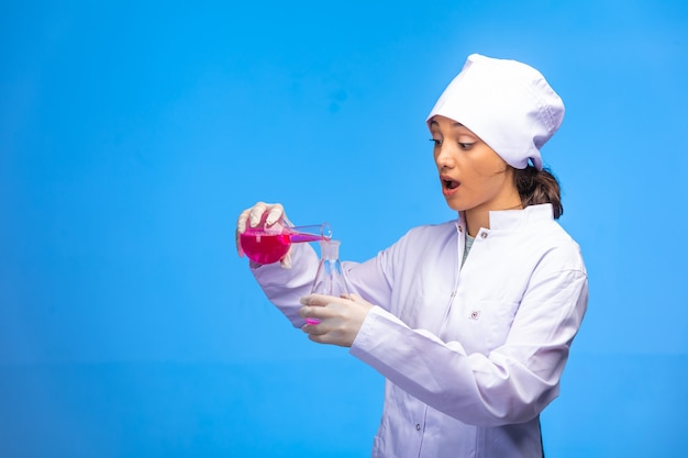 Jonge verpleegster in wit uniform controleert biologische reactie en wordt verrast