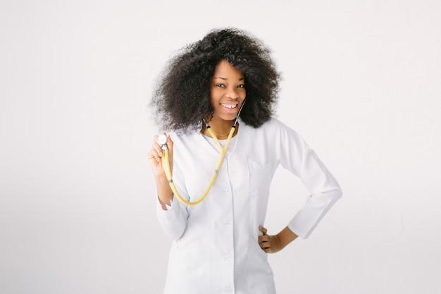 Jonge verpleegster portret. verpleegkundige, gezondheidszorg en geneeskunde, arts. een vrouwelijke arts met een stethoscoop in het ziekenhuis op een witte achtergrond