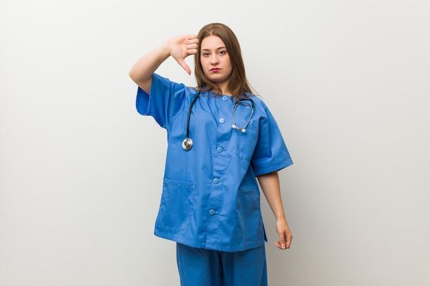 Jonge verpleegstersvrouw die een afkeergebaar tonen, duimen neer. meningsverschil concept.