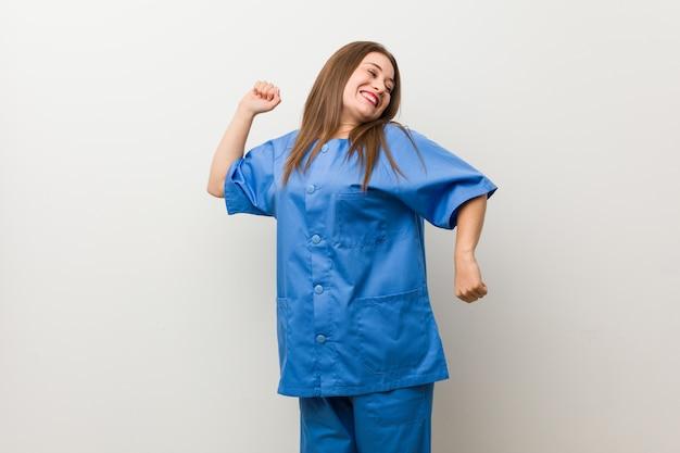 Jonge verpleegstersvrouw tegen een witte muur die en pret danst heeft.