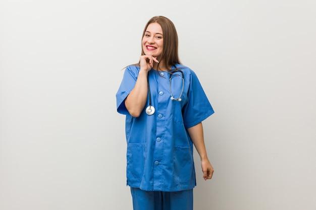 Jonge verpleegstersvrouw tegen een witte muur die gelukkig en zeker, wat betreft kin met hand glimlacht.