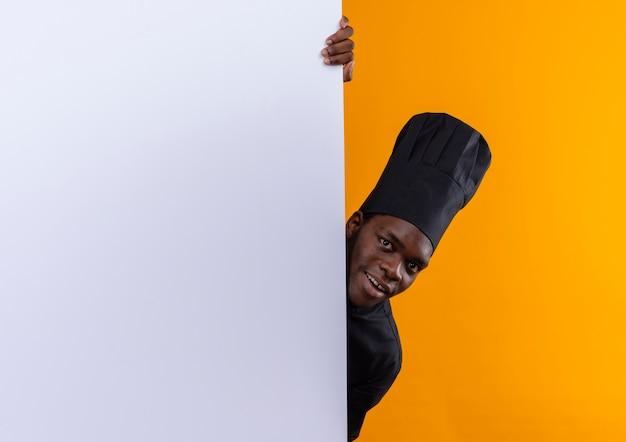 Jonge verrast afro-amerikaanse kok in uniform chef-kok staat achter witte muur geïsoleerd op oranje ruimte met kopie ruimte