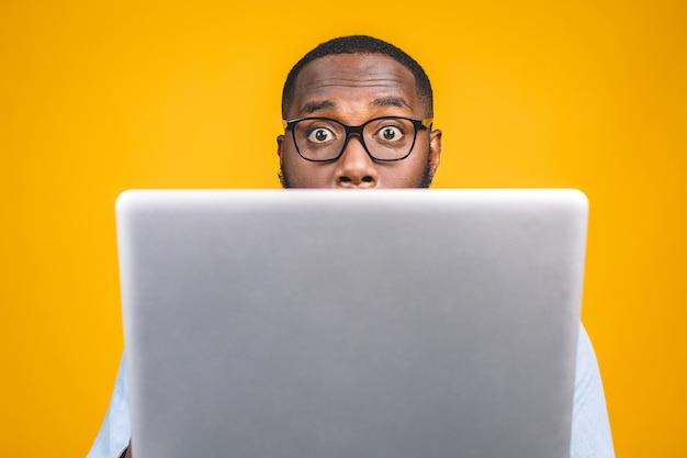 Jonge verrast afro-amerikaanse man permanent en met behulp van laptopcomputer
