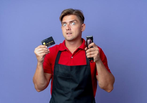Jonge verrast blonde mannelijke kapper in uniform houdt creditcard en haartrimmer geïsoleerd