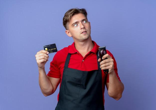 Jonge verrast blonde mannelijke kapper in uniform houdt creditcard en haartrimmer