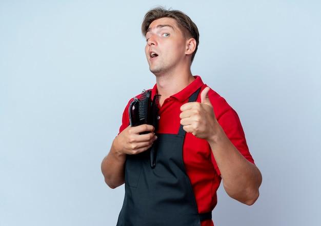 Jonge verrast blonde mannelijke kapper in uniform thumbs up kapper tools geïsoleerd op een witte ruimte met kopie ruimte te houden
