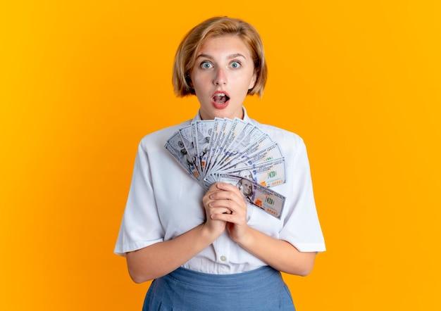 Jonge verrast blonde russische meisje houdt geld kijken camera geïsoleerd op een oranje achtergrond met kopie ruimte