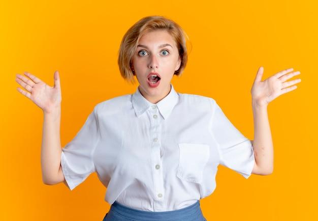 Jonge verrast blonde russische meisje staat met opgeheven handen geïsoleerd op een oranje achtergrond met kopie ruimte
