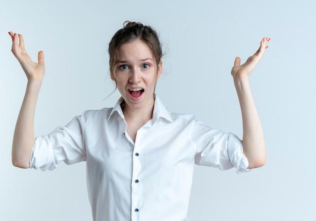 Jonge verrast blonde russische meisje staat met opgeheven handen omhoog geïsoleerd op witte ruimte met kopie ruimte