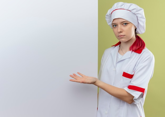 Jonge verrast blonde vrouwelijke chef-kok in eenvormige chef-kok staat erachter en wijst naar de witte muur op zoek geïsoleerd op groene muur