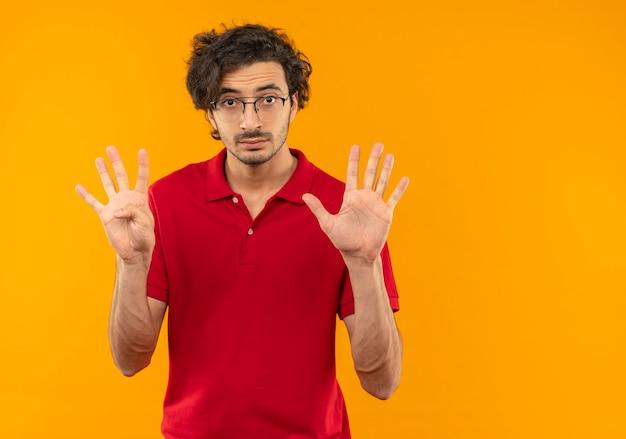 Jonge verrast man in rood shirt met optische bril gebaren negen met vingers geïsoleerd op oranje muur