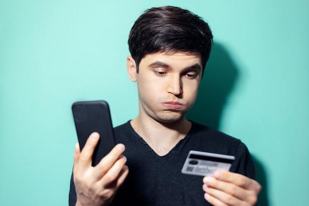 Jonge verrast man met smartphone en creditcard in de hand op muur van aqua menthe kleur.