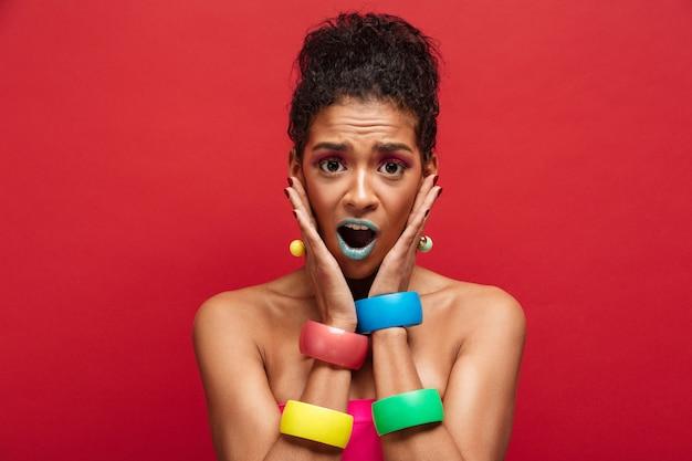 Jonge verrast mulat vrouw wordt helder en stijlvol grijpen gezicht dragen armbanden op armen, over rode muur