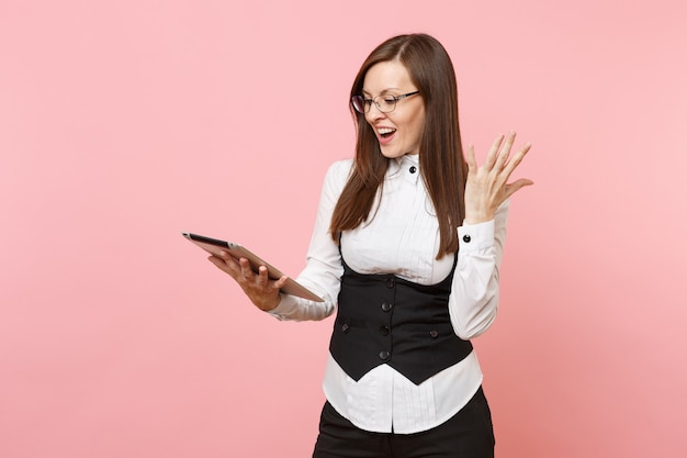 Jonge verrast succesvolle zakenvrouw houden met behulp van tablet pc-computer verspreiden handen geïsoleerd op pastel roze achtergrond. dame baas. prestatie carrière rijkdom concept. kopieer ruimte voor advertentie.