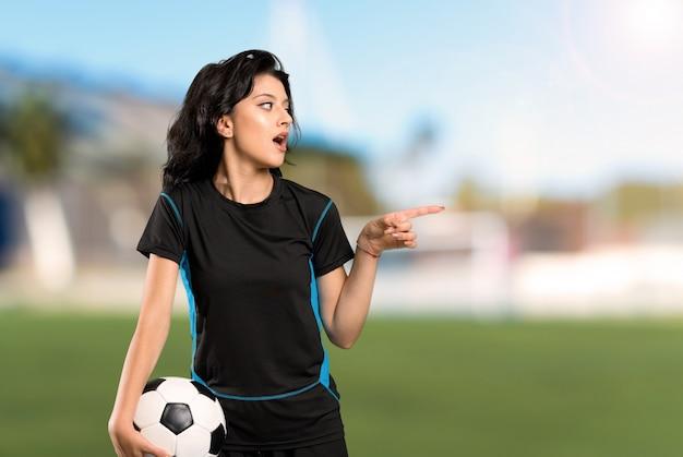 Jonge verrast voetballervrouw en in openlucht richtend de vinger aan de kant op