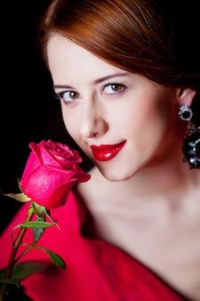 Jonge verrast vrouw in rode victoriaanse tijdperk kleding met rode roos op donker