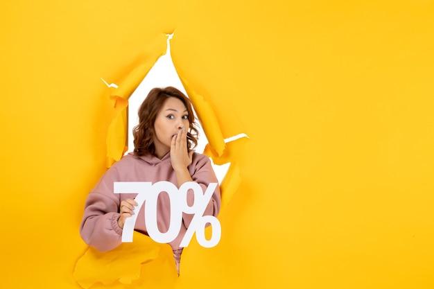 Jonge verraste mooie dame die zeventig procentteken op gele gescheurde doorbraakachtergrond toont
