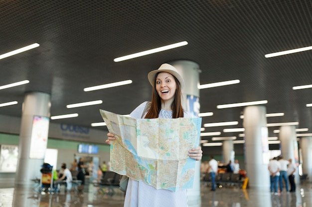 Jonge verraste reiziger toeristische vrouw in hoed met papieren kaart, route zoeken en wachten in lobby hal op internationale luchthaven