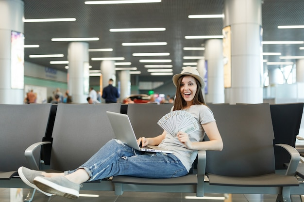 Jonge verraste reizigerstoeristenvrouw die aan laptop werkt, houdt een bundel dollars contant geld in de lobby op de internationale luchthaven
