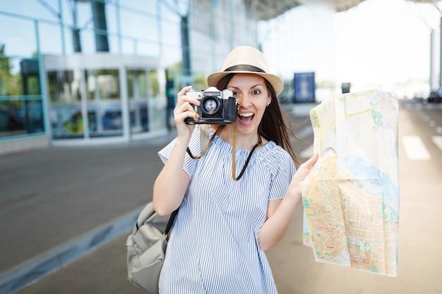 Jonge verraste reizigerstoeristenvrouw maakt foto's op retro vintage fotocamera, houdt papieren kaart vast op internationale luchthaven
