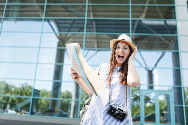 Jonge verraste reizigerstoeristenvrouw met retro vintage fotocamera, papieren kaart, zich vastklampend aan het hoofd op de internationale luchthaven