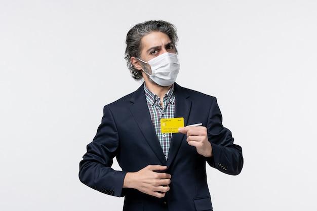 Jonge verraste serieuze kantoorassistent in pak met masker en zijn bankkaart op geïsoleerde witte achtergrond white