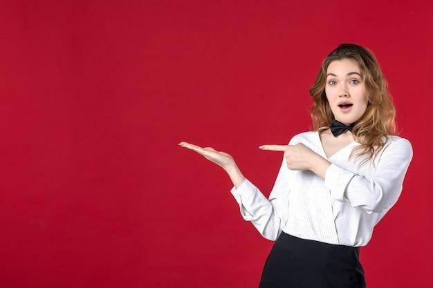 Jonge verraste serveerster vrouw vlinder in de nek en wijst iets aan de rechterkant op rode achtergrond