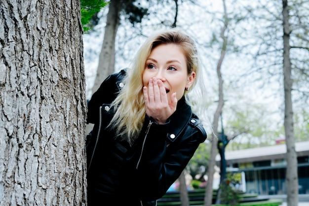Jonge verraste vrouw die achter de boom in een park verbergt dat zwarte leerjasje draagt