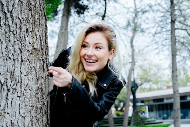 Jonge verraste vrouw die achter de boom verbergt die door vinger in een park wijst dat op zwart leerjasje draagt