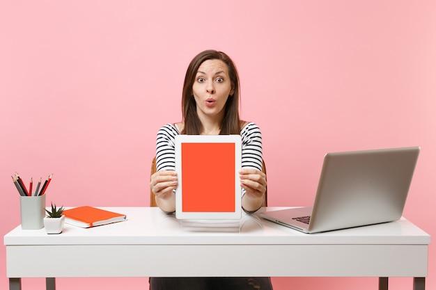 Jonge verraste vrouw die een tabletcomputer met een leeg leeg scherm laat zien, zit aan een wit bureau met een moderne pc-laptop
