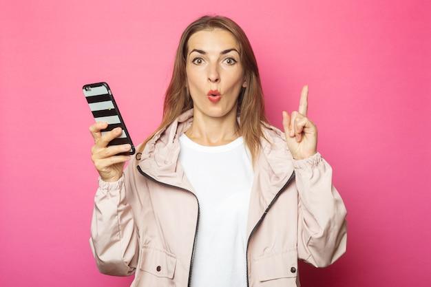 Jonge verraste vrouw die een telefoon houdt, geïsoleerd roze.