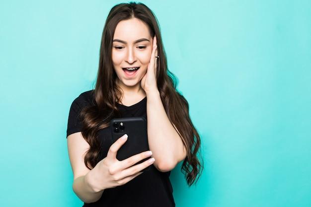 Jonge verraste vrouw met telefoon die op turkooise muur wordt geïsoleerd