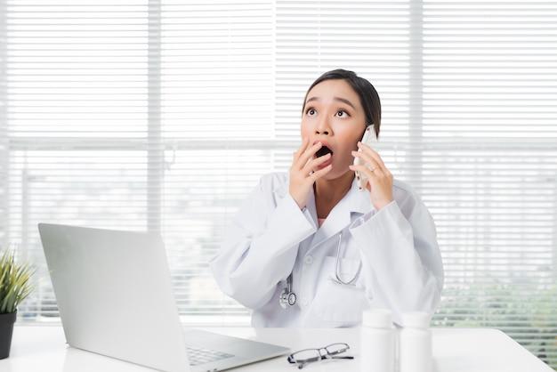 Jonge verraste vrouwelijke arts die aan een bureau zit en met een laptop werkt
