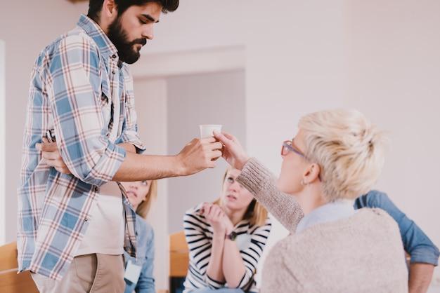 Jonge verslaafde mensen die een gestreste situatie hebben terwijl ze samen zitten op speciale groepstherapie. boos bebaarde man die water neemt om te kalmeren na zijn bekentenis.