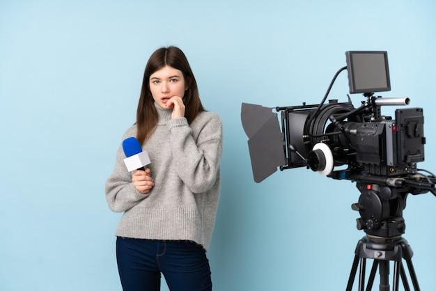 Jonge verslaggeversvrouw die een microfoon houden en nieuws zenuwachtig en doen schrikken